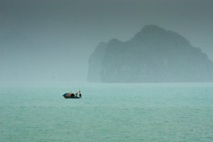 A lonely boat on a rainy day in Ha Long Bay, Vietnam.